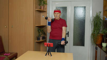 Senior elderly man exercising. Old grandfather doing workout with dumbbells, training, fitness, sport activity at home. Trainer shoots video blog trainings online vlog course during coronavirus