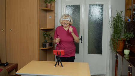 Mature woman fitness trainer coach recording video online workout course with a smartphone live streaming sport exercises at home. Senior grandmother live stream blog, vlog during coronavirus lockdown