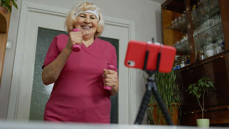Senior elderly woman watching online distance workout exercises with dumbbells on mobile phone and training, fitness, sport activity at home. Mature grandmother during coronavirus lockdown quarantine