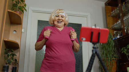 Senior elderly woman exercising. Old grandmother doing workout with dumbbells, training, fitness, sport activity at home. Trainer shoots video blog trainings online vlog course during coronavirus