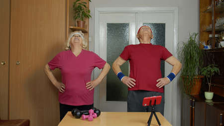 Retired senior couple man woman doing workout, training, fitness, sport activity exercises at home. Elderly grandmother grandfather starting live stream, vlog, blog, online distance internet course 版權商用圖片