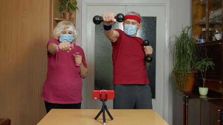 Senior elderly couple exercising. Old grandmother grandfather doing workout, training, fitness, sport activity at home. Trainers shoots video blog trainings online vlog during coronavirus lockdown