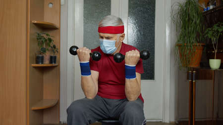Senior elderly caucasian man in sportswear in living room, making weight lifting dumbbells exercising at home. Active old retiree doing workout, training, fitness, sport activity during coronavirus