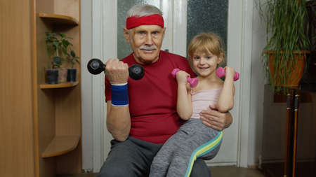 Child kid girl and senior grandfather in sportswear making sports workout at home. Active old mature man with granddaughter doing fitness weightlifting exercises with dumbbells. Healthy lifestyle