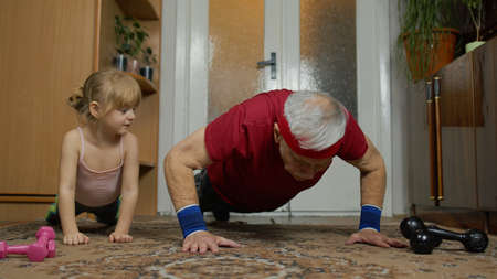 Granddaughter and mature grandfather in sportswear making sports workout, training at home. Active old senior man with child kid girl doing fitness push-ups exercises. Healthy lifestyle