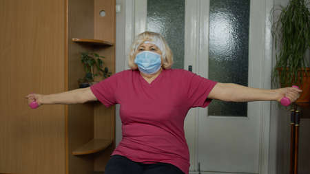 Senior mature grandmother woman in sportswear doing weightlifting dumbbell exercising at home. Active pensioner in mask doing workout, training, fitness, sport activity during coronavirus lockdown