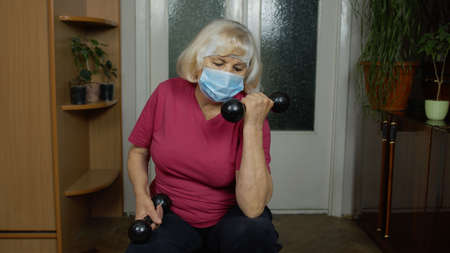Retired senior woman in medical mask doing workout, training, fitness, sport activity exercises at home. Elderly old grandmother making weight lifting dumbbells exercising during coronavirus lockdown 版權商用圖片