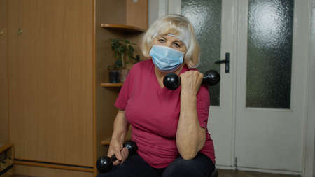 Senior elderly caucasian woman in sportswear in living room, making weightlifting dumbbells exercising at home. Active old retiree doing workout, training, fitness, sport activity during coronavirus