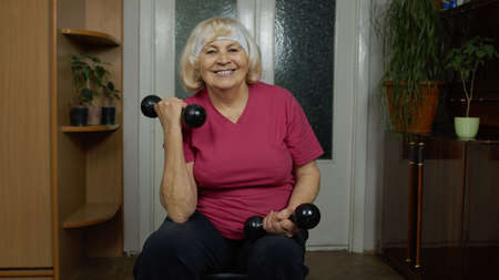 Senior mature grandmother woman in sportswear doing weightlifting dumbbell exercising at home. Active retired pensioner lady doing workout, training, fitness, sport activity. Healthy lifestyle concept 版權商用圖片