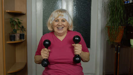 Senior mature grandmother woman talking and doing weightlifting dumbbell exercising at home. Active retired pensioner doing workout training, fitness sport activity. Vlog, blog, online distance course