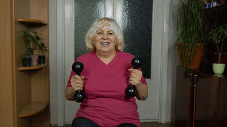 Senior elderly caucasian woman in sportswear making weightlifting dumbbells exercising at home. Active grandmother retiree talking and doing workout, training, fitness, sport activity. Blog, vlog
