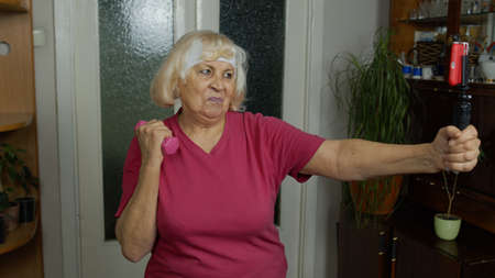 Retired happy senior woman doing workout, training, fitness, sport activity exercises at home. Elderly grandmother starting live stream, vlog, blog, online distance course during coronavirus lockdown