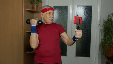 Senior elderly man exercising. Old grandfather doing workout with dumbbells, training, fitness, sport activity at home. Trainer shoots selfie video blog trainings online vlog course during coronavirus
