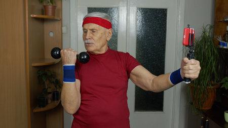 Retired senior man doing workout, training, fitness, sport activity exercises at home. Elderly grandfather starting live stream, vlog, blog, online distance internet course during coronavirus lockdown