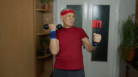 Mature man fitness trainer coach recording video online workout course with a smartphone live streaming sport exercises at home. Senior grandfather live stream, blog, vlog during coronavirus lockdown