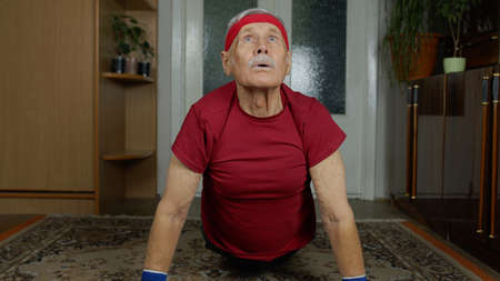 Senior elderly caucasian man in sportswear in living room, making morning push-up exercising at home. Active old mature grandfather retiree doing workout, training, fitness sport activity
