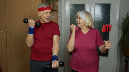 Senior elderly couple man woman exercising. Old grandmother grandfather doing workout with dumbbells, training, fitness, sport activity at home. Trainers shoots video blog trainings online vlog course 版權商用圖片