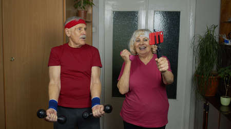 Senior elderly couple man and woman watching online workout exercises on mobile phone and training with dumbbells together at home. Mature old grandmother and grandfather during coronavirus lockdown