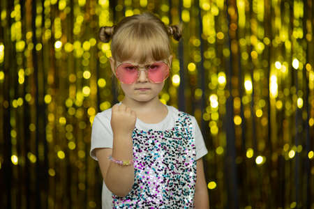 Funny child trying to fight at camera, boxing with expression. Little fun blonde kid teen teenager girl 4-5 years old in sunglasses isolated on background with foil fringe golden curtain in studio