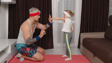 Retro style athletic man coach working out with child kid girl. Gray-haired bearded sportsman guy trainer father doing boxing exercises with daughter at home on mat. Indoors family sport workout