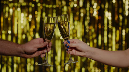Couple raising toast with glasses of wine or cocktail. Two hands with glasses of champagne making cheers on gold background. Celebration of business success, wedding, Christmas, anniversary, birthday