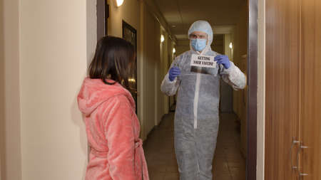 Medical worker in protective suit with text on paper, vaccine ampoule and syringe in hands visiting woman at home offering vaccination