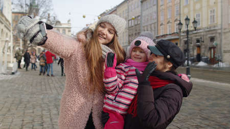 Two young smiling women tourists taking selfie photos portrait, video conferencing on mobile phone with adoption child girl on city street. Lesbian couple talking, embracing. Winter holidays traveling
