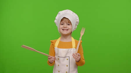 Little charming child girl dressed in apron and hat like chef cook dancing with wooden fork and spatula on chroma key background. Concept of nutrition, family cooking school, children education, game
