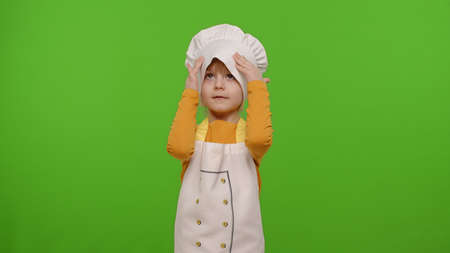 Child girl kid dressed as professional cook chef smiling, crosses arms and looks intently at camera on chroma key background. Nutrition, cooking school, education, food. Fun and humor. Copy-space