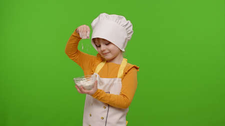 Little charming child girl dressed in apron and hat like chef cook stir the flour in a plate on chroma key background. Concept of nutrition, family cooking school, children education game. Copy-space