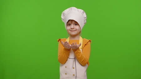 Joyful smiling child girl kid dressed as professional cook chef with flour in hands looking at camera on chroma key background. Nutrition, cooking school, education, food. Fun and humor. Copy-space