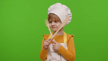 Dissatisfied child girl kid dressed as professional cook chef with wooden fork and spatula, showing symbol of rejection, disagreement on chroma key background. Nutrition, cooking education food school