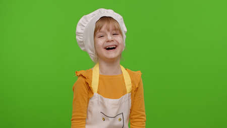 Child girl dressed cook chef baker in apron and hat laughing out loud after hearing funny joke, feeling positive carefree amused isolated on chroma key background. Cooking school, children education