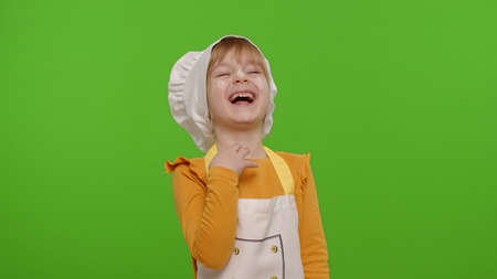 Little charming child girl dressed in apron and hat like chef cook laughing out loud after hearing ridiculous anecdote, funny joke, feeling carefree amused, positive lifestyle on chroma key background