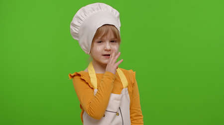 Child girl kid dressed as professional cook chef holding finger on her lips on chroma key background. Gesture of shhh, hush, secret, silence. Nutrition, cooking school, education, food. Fun and humor
