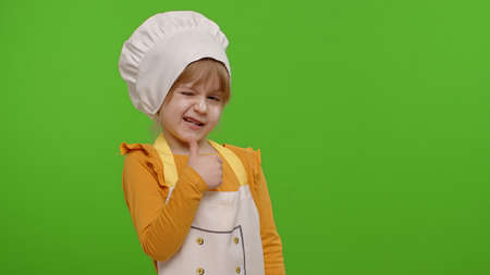 Funny Caucasian preschooler child girl dressed cook chef baker in apron and hat showing thumbs up, fooling around isolated on chroma key background. Slow motion. Cooking school, children education 版權商用圖片