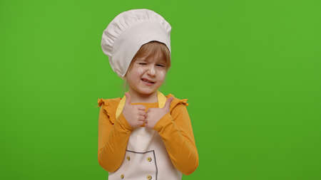 Child girl kid dressed as professional cook chef showing thumbs up, smiling, looking happy at camera on chroma key background. Nutrition, cooking school, education, food. Fun and humor. Copy-space