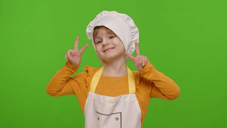 Little child girl dressed in apron and hat like chef cook showing victory sign, hoping for success and win, doing peace gesture and smiling with kind optimistic expression on chroma key background