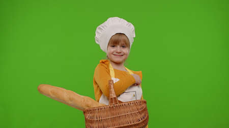 Child girl kid dressed as professional cook chef showing basket with baguette and bread, smiling, sniffing, looking at camera on chroma key background. Nutrition, cooking school, education, food