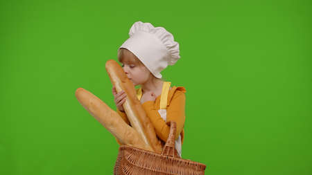 Little child girl dressed in apron and hat like chef cook showing basket with baguette and bread, smiling, sniffing on chroma key background. Nutrition, family cooking school, children education, game