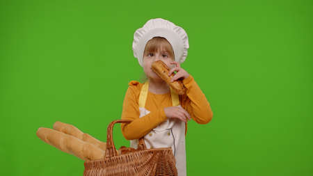 Child girl dressed in apron like chef cook showing basket with baguette and bread, smiling, sniffing, eating bun with cream on chroma key background. Nutrition, cooking school, children education