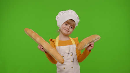 Funny Caucasian child girl dressed like cook chef baker in apron and hat sniffing two baguettes, fooling around, making faces isolated on chroma key background. Cooking school, children education