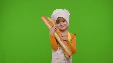 Child girl kid dressed as professional cook chef baker showing and sniffing two fresh baguettes, smiling, waving head in agreement on chroma key background. Nutrition, cooking school, education, food 版權商用圖片