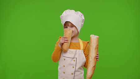 Little joyful child girl dressed in apron and hat like chef cook eating fresh tasty baguette, fooling around on chroma key background. Concept of nutrition, family cooking school, children education