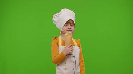 Little joyful child girl dressed in apron and hat like chef cook eating fresh tasty baguette, making faces on chroma key background. Concept of nutrition, family cooking school, children education 版權商用圖片