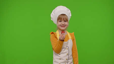 Little charming child girl dressed in apron like chef cook eats delicious fresh strawberries and laughing out loud on chroma key background. Nutrition, family cooking school, children education