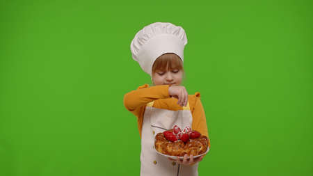 Portrait of little child girl kid dressed as professional cook chef sprinkle strawberry pie with icing sugar isolated on chroma key background. Concept of nutrition food, cooking school, education