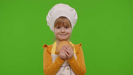 Little joyful child girl 5-6 years old dressed in apron and hat like chef cook eating tasty bun on chroma key background. Concept of nutrition, family cooking school, children education. Copy-space