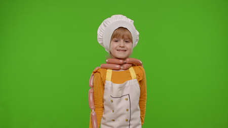 Funny Caucasian teen child girl dressed as cook chef in apron dancing with sausages, fooling around, making faces isolated on chroma key background. Slow motion. Cooking school, children education