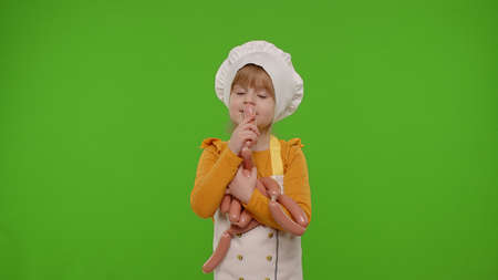 Child girl kid dressed as professional cook chef stay with sausages, fooling around, making faces, showing thumbs up on chroma key background. Nutrition, cooking school, education, food. Fun and humor